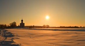 Härlig vintersoluppgång på landskapet med den ortodoxa kyrkan arkivbild