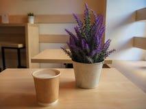 Härlig violett lavendel i en liten hink för järn och en kopp kaffe på trätabellen royaltyfri fotografi