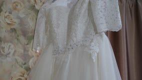 Härlig vit bröllopsklänning som hänger på hängare på fönstret stock video