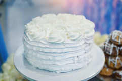 Härlig vit bröllopstårta med blommor på en tabell Arkivbilder