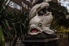 Härlig vit fisk som packar gatalampan i London, en charac in Arkivbilder