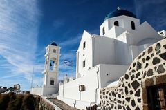Härlig vit kyrka med blåa kupoler och den grekiska flaggan på ön royaltyfria bilder