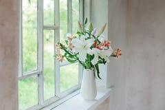 Härlig vit lilja i vas på fönsterbräda Arkivbild