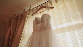 Härlig vit lyxig bröllopsklänning på hängare på bakgrunden av ett fönster stock video
