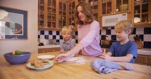 Härlig vit moder som förbereder kakadeg med hennes pojkar arkivbild