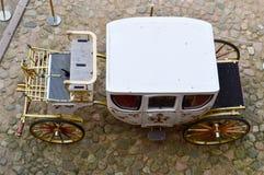 Härlig vit sniden rik vagn för träkunglig person med stora hjul som dekoreras med guld- modeller bredvid den gamla europén royaltyfri fotografi