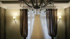 Härlig vit stilfull bröllopsklänning på hängare på bakgrunden av ett fönster i lluxury lägenheter lager videofilmer
