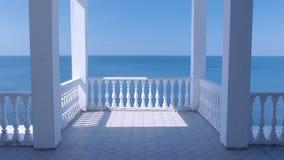 Härlig vit terrass med dekorativ staket- och för havssiktsom strand arkivfilmer