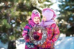 Härlig vit vinterbild i entäckt skog i natur med barn Två systrar kopplar samman i ljusa omslag, och hattar är Royaltyfria Bilder