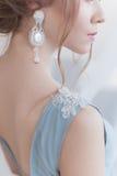 Härlig volymfrisyr för en brud i en försiktig blå ljus klänning med stora örhängen och prydnad i hår Arkivfoto