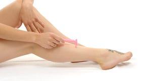 Härlig vuxen caucasian kvinna som rakar ben med rakkniven Arkivbild