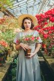 Härlig vuxen flicka i ett azaleaväxthus som drömmer i en härlig retro klänning och hatt fotografering för bildbyråer
