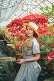 Härlig vuxen flicka i ett azaleaväxthus som drömmer i en härlig retro klänning och hatt royaltyfri foto