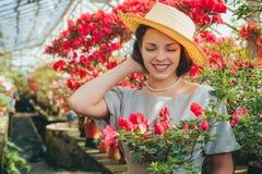 Härlig vuxen flicka i ett azaleaväxthus som drömmer i en härlig retro klänning och hatt royaltyfri bild