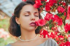 Härlig vuxen flicka i ett azaleaväxthus som drömmer i en härlig retro klänning och hatt arkivfoto