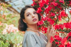 Härlig vuxen flicka i ett azaleaväxthus som drömmer i en härlig retro klänning och hatt arkivfoton