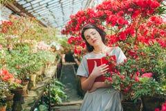 Härlig vuxen flicka i ett azaleaväxthus som läser en bok och drömmer i en härlig retro klänning arkivbilder