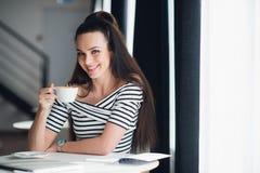 Härlig vuxen kvinna med ett perfekt leende och vita tänder som sitter i ett kafé nära ett fönster och ett innehav per koppen kaff Fotografering för Bildbyråer