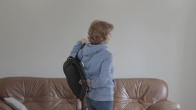 Härlig vuxen le kvinna som tar en ryggsäck från soffan som går på en tur arkivfilmer