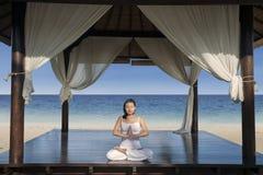 Härlig yogakvinna på den lyxiga strandsemesterorten Arkivfoto