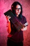 Härlig yrkesmässig Gamerflicka med tangentbordet Exponeringsglas och le f?r tillf?llig gullig Geek b?rande Cybere-sport internet arkivbilder