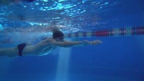 Härlig yrkesmässig simmare som gör fjärilsslaglängden i pöl med rikt blått vatten, skott från undervattens- Arkivfoto