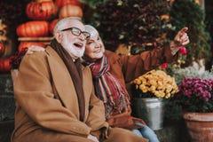 Härliga äldre par som sitter på trappa och ser något som är rolig royaltyfri fotografi