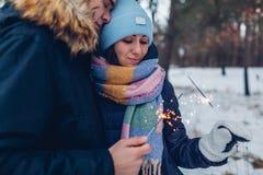 Härliga älska brinnande tomtebloss för par i vinterskogjul och begrepp för nytt år royaltyfri bild