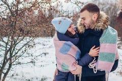 Härliga älska par som går och kramar, i värme för vinterskogfolk som täckas med filten royaltyfria bilder