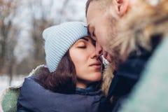 Härliga älska par som går och kramar, i värme för vinterskogfolk som täckas med filten close upp royaltyfria foton