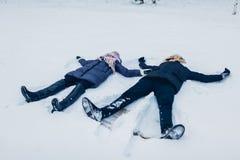 Härliga älska par som gör snöänglar i vinterskogen som ligger i snö Folk som har roligt utomhus royaltyfri fotografi