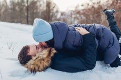 Härliga älska par som ligger på snö och utomhus kysser i vinterskogfolk som har gyckel royaltyfri foto
