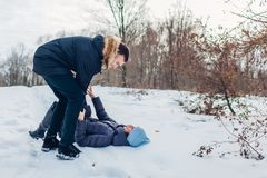 Härliga älska par som spelar i vinterskogmannen som rymmer och skjuter flickvännen i snö Folk som har roligt utomhus royaltyfria bilder