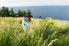 härliga älska par som vilar i sommarfält på stort gräs och att smeka sig och att kyssa förbunden gräs royaltyfria foton