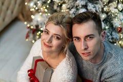 Härliga älska ungdomarkramar på julgranbakgrund royaltyfria foton