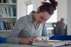 Härliga anmärkningar för för rödhårig manflickaarbete och handstil på skrivbordintelligensen royaltyfria bilder