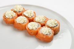 Härliga aptitretande rullar av sushi på en vit platta Arkivbilder