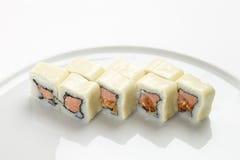 Härliga aptitretande rullar av sushi på en vit platta Arkivfoton