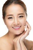 Härliga asiatiska den rörande skönhetkvinnan gör perfekt hud Arkivfoto