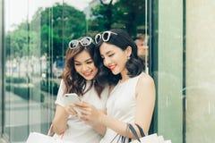 Härliga asiatiska flickor med shoppingpåsar genom att använda smartphonen Fotografering för Bildbyråer