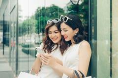 Härliga asiatiska flickor med shoppingpåsar genom att använda smartphonen på arkivbild