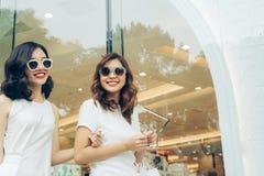 Härliga asiatiska flickor med shoppingpåsar som går på gatan Arkivbilder