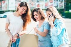 Härliga asiatiska flickor som rymmer shoppingpåsar, använder en smart telefon och ler, medan stå utomhus shopping- och turismbegr Arkivfoto