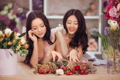 Härliga asiatiska kvinnablomsterhandlare med buketten av blommor i blommalager Royaltyfria Bilder