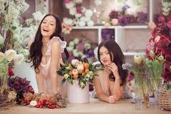 Härliga asiatiska kvinnablomsterhandlare med buketten av blommor i blommalager Arkivbilder