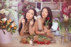 Härliga asiatiska kvinnablomsterhandlare med buketten av blommor i blommalager Royaltyfri Fotografi