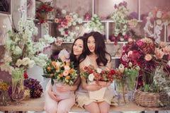 Härliga asiatiska kvinnablomsterhandlare med buketten av blommor i blommalager Arkivfoton
