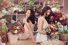 Härliga asiatiska kvinnablomsterhandlare med buketten av blommor i blommalager Royaltyfri Foto