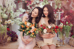 Härliga asiatiska kvinnablomsterhandlare med buketten av blommor i blommalager Royaltyfria Foton