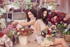 Härliga asiatiska kvinnablomsterhandlare som arbetar i blommalager med mycket vår, blommar Royaltyfri Fotografi